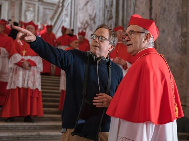 Mann (Regisseur) zeigt mit dem Finger nach links, neben ihm steht ein Kardinal und schaut in dieselbe Richtung