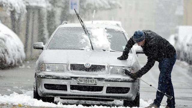 Ein Mann befreit die Scheinwerfer seines Autos von Eis und Schnee.