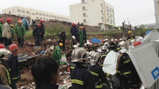 Rettungskräfte suchen unter den Trümmern nach Verletzten, man sieht Erdmassen und zertrümmerte Reste von Häusern.