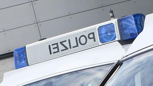 Bildausschnitt eines Polizeifahrzeugs, zu sehen ist das Blaulicht auf dem Dach und die spiegelverkehrte Aufschrift «Polizei».