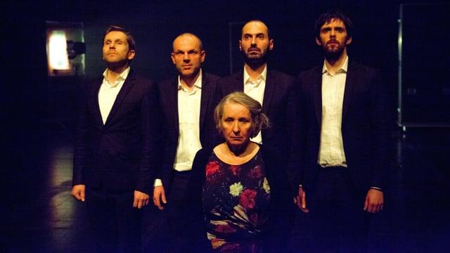 Eine Frau sitzt auf einem Stuhl in einem dunklen Raum, dahinter stehen vier Männer in schwarzem Anzug und weissem Hemd.