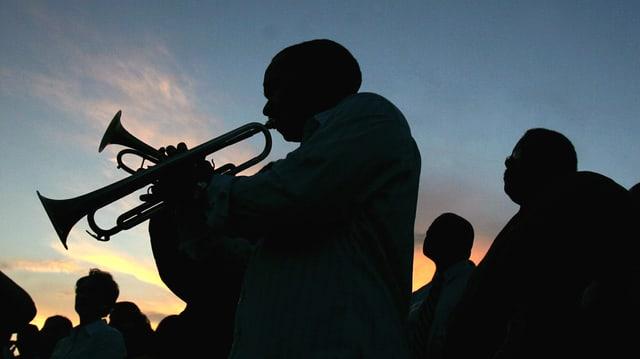 Schwarze Männer: eine Marching Band im Abendgegenlicht.