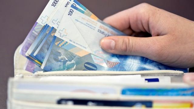 Hand nimmt Banknoten aus Geldbeutel.