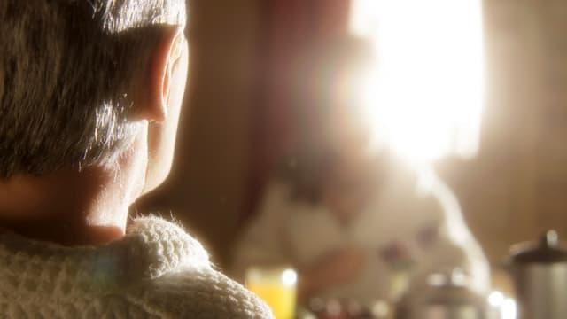 Im Vordergrund der Hinterkopf einer Frau mit kurzen Haaren, ihr gegenüber eine andere Frau, die durch das Licht hinter ihr kaum sichtbar ist.