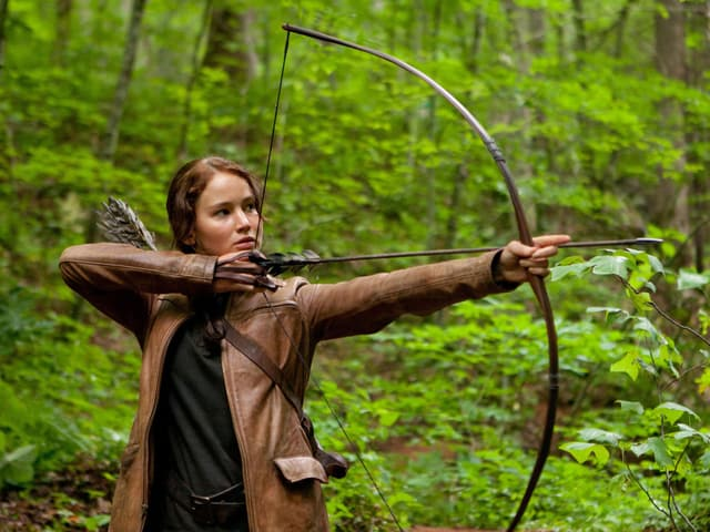 Eine Frau steht im Wald und zielt mit einem Pfeilbogen.
