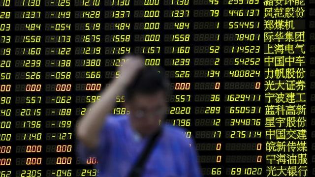 In um avant ina tavla cun infurmaziuns da la bursa a Shanghai.