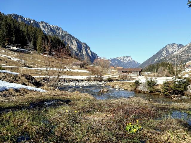 Ein Bach in der Mitte sammelt das Wasser des schmelzenden Schnees, im Hintergrund Berge und eine Hütte.