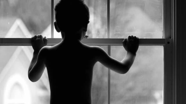 Kind von hinten, das vor einem geschlossenen Fenster steht.