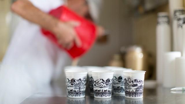 In einer Sennere giesst ein Angestellter aus einem Krug frisches Joghurt in Becher.