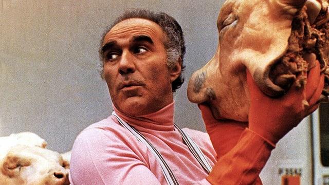 Ein Mann mit einem Schweinskopf in der Hand.