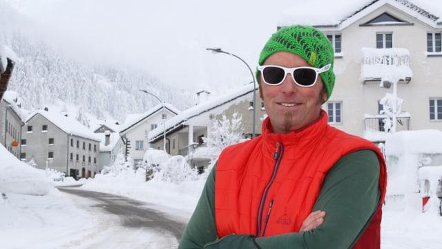 Mann in orangem Gilet, grüner Mütze und weisser Sonnenbrille, dahinter verschneites Dorf