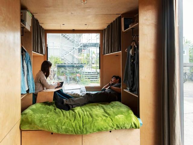 Mann und Frau auf grüner Decke in Tiny House.