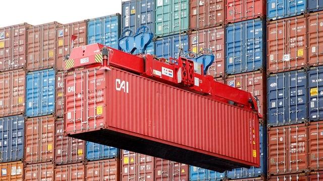 Roter Schiffscontainer hängt an Kranseilen vor einer Wand weiterer Container