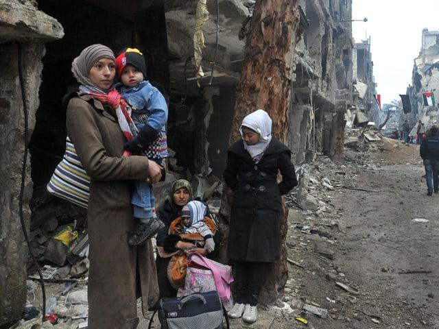 Frauen stehen mit Kindern auf dem Arm an einer Strassenecke.