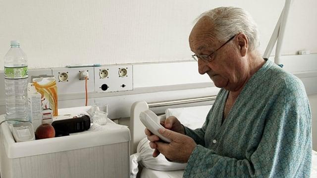 Älterer Mann sitzt auf dem Spitalbett und hält einen Telefonhörer in der Hand