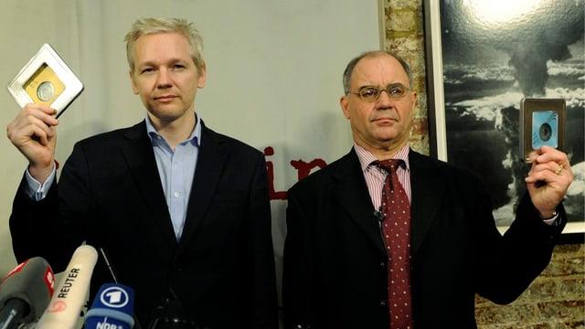 Julian Assange und Rudolf Elmer zeigen an einer Medienkonferenz 2011 die Daten-CDs.