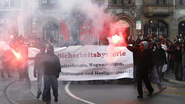 Blick auf eine Demonstration mit Demonstranten, die sogenannte Pyros abbrennen und ein Transparent gegen das Hooligan-Gesetz halten.