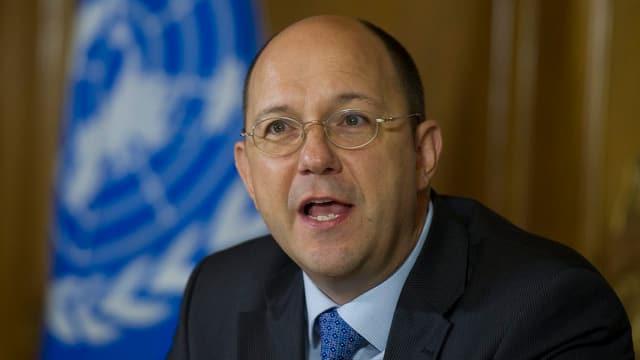 Mann mit Glatze, Brille und Anzug hält eine Rede