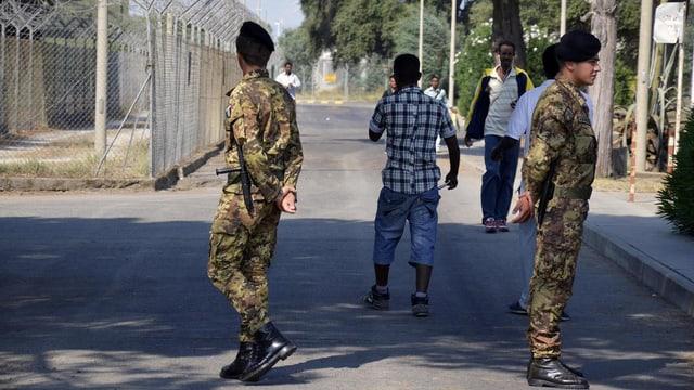 2013 patroullieren Soldaten vor dem Flüchtlingszentrum bei Crotone.