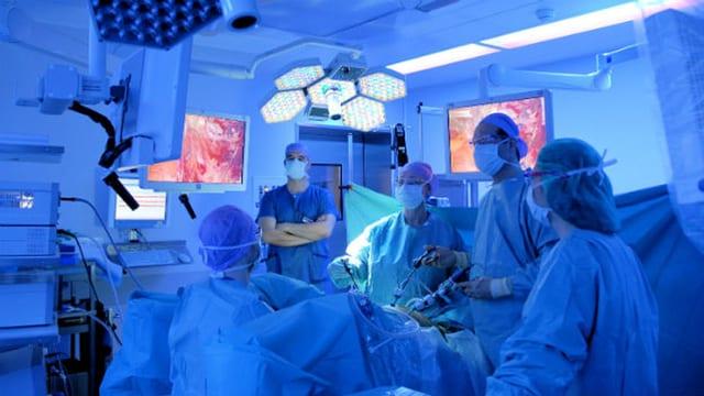 Ein Operationsteam des Kantonsspitals Aarau operiert in blauem Licht.