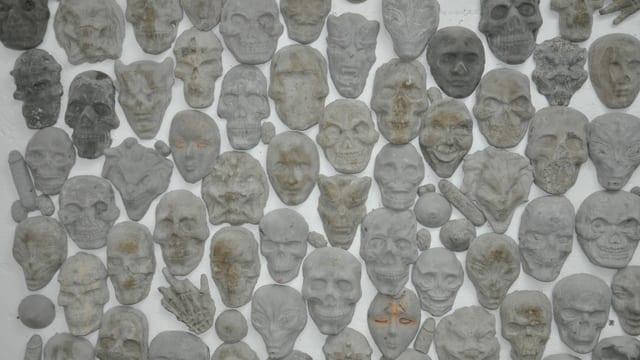 diversas fatschas e chavazzas, skelets da betun che pendan vid ina paraid alva