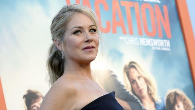 Christina Applegate trägt ein schulterfreies, schwarzes Kleid und blickt in die Ferne.