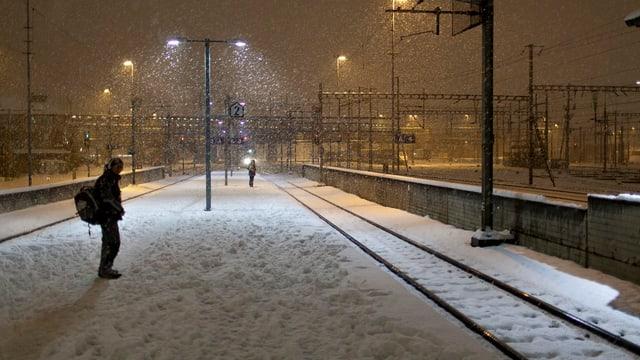 Pendler steht auf verschneitem Perron am Bahnhof