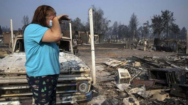 Frau steht vor den Überresten verbrannter Autos und Häuser.