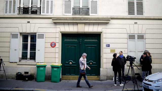 Journalisten vor einem Haus mit einer grünen Türe.