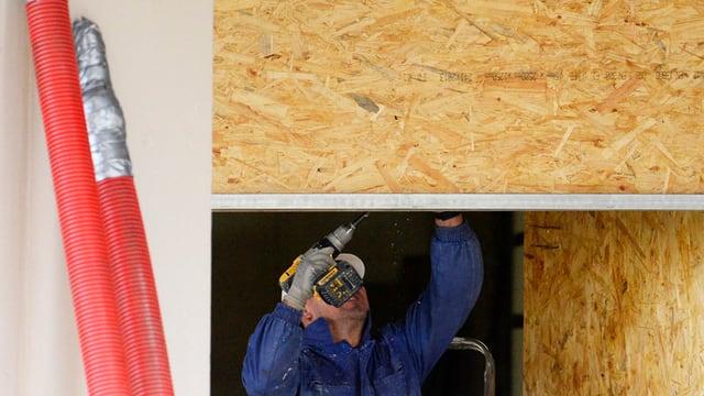 Ein Handwerker bohrt in eine Holzplatte an der Decke.