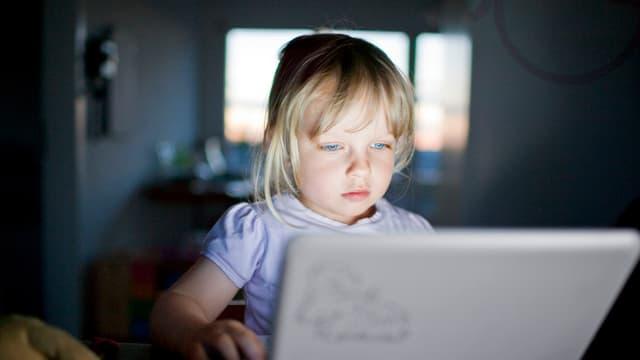 In uffant guarda en in laptop