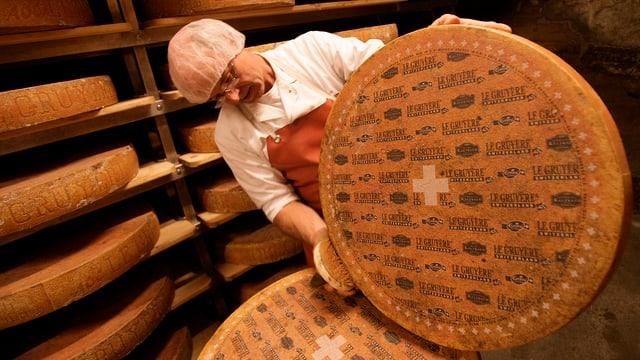 Mann «wäscht» einen grossen, runden Käse.