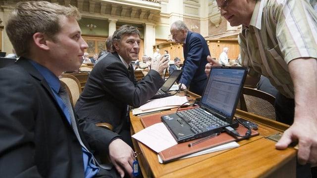 Nationalrat Lukas Reimann mit anderen Nationalräten im Saal in Bern