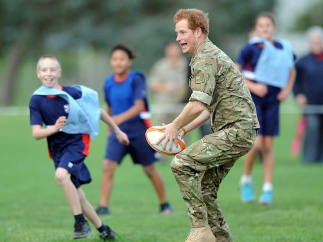 Prinz Harry spielt mit einem Rugby-Ball.