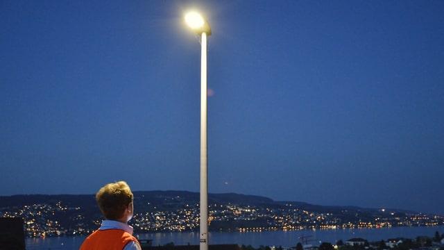 Eine Strassenlampe läuchtet, im Hintergrund der Zürichsee.