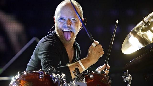 Lars Ulrich am Schlagzeug sitzend mit herausgestreckter Zunge.