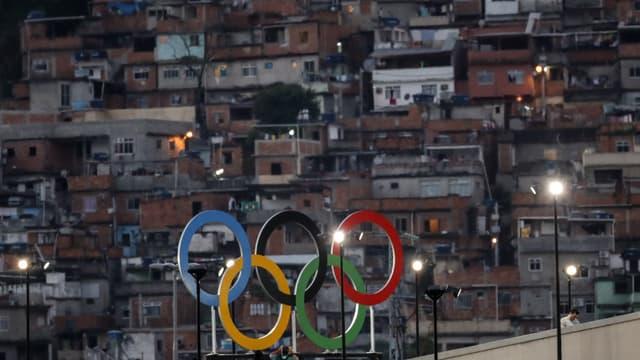 Die Olympischen Ringe vor einer Favela Rios.