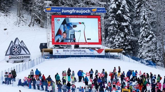 Zuschauer stehen am Bern und schauen auf eine Leinwand.