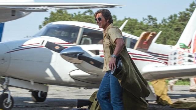 Barry Seal trägt Waffen in ein Flugzeug.
