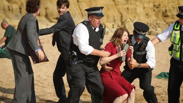 Polizisten halten eine Frau im roten Kleid im Arm