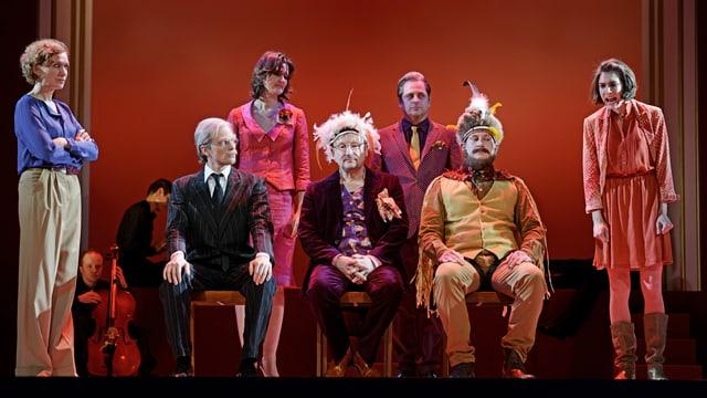 Sitzende und stehende Personen, farbig angezogen, einige mit Federn auf dem Kopf.
