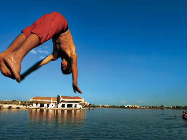 Ein Junge in roten Badehosen springt in einen See.
