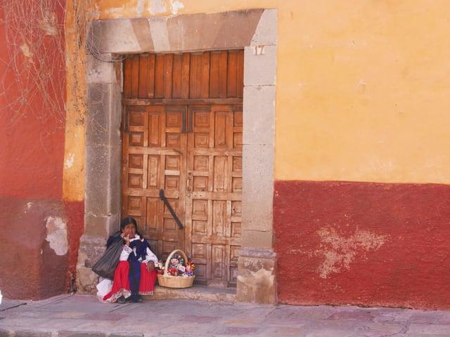 Eine Frau sitzt vor der Tür.