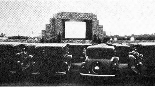 Ein Schwarzweissbild aus den 1930er-Jahren. Eine grosse Leinwand, davor viele alte Autos.
