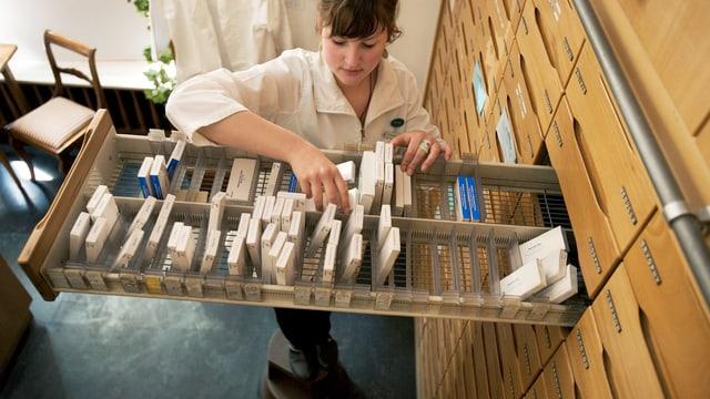 Apothekerin nimmt Medikamente aus einer langen Schublade