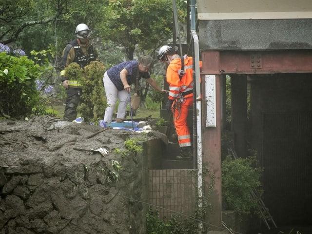 Feuerwehrmänner evakuieren eine Anwohnerin im betroffenen Gebiet.