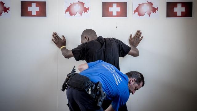 Ein Angehöriger des Grenzwachtkorps durchsucht am Zoll des Bahnhofs Chiasso einen Migranten.