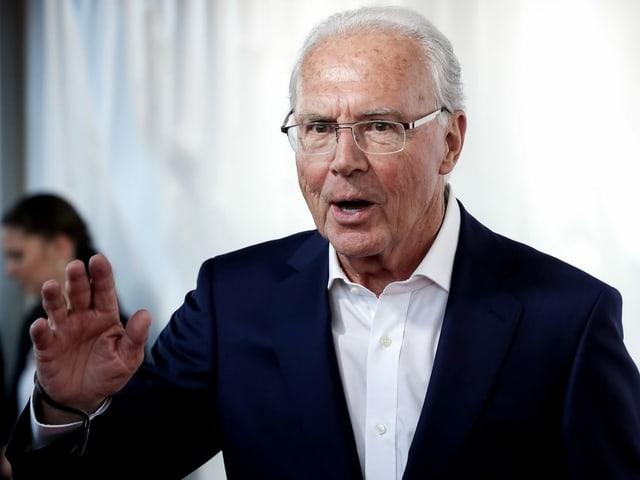 Franz Beckenbauer grüsst an einer Tagung.