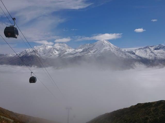 Gondeln und ein Bergpanorama mit Schnee und blauem Himmel.