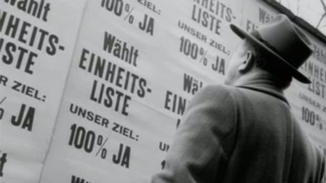 Mann steht vor Plakatwand mit nur einer Wahlliste.